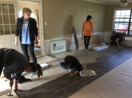 Presbyterian Disaster Assistance volunteers laying new flooring in the living room and kitchen